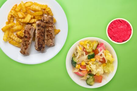 pork ribs and potatoes on a white plate with salad and sauce on a lime background. Top view of fast food. unhealthy food.flat lay Banco de Imagens
