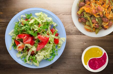 vegetarian food . salad of cabbage tomato on a light blue plate on a wooden background. healthy food Imagens