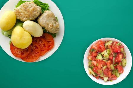 cutlet with potatoes on a white  plate. cutlet with potatoes on a green background.homemade food. flat lay