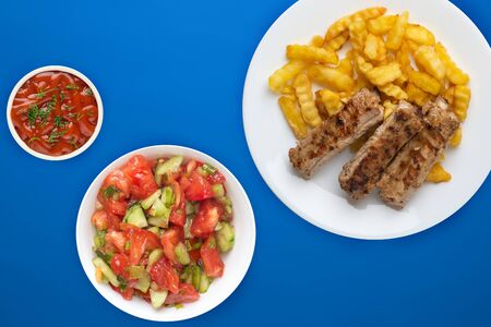 pork ribs and potatoes on a white plate with salad and sauce on a blue background. Top view of fast food. unhealthy food.flat lay
