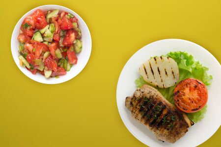 grilled pork with potatoes and tomatoes on a yellow background. fried pork on a white plate with salad and sauce top view.flat lay Banco de Imagens