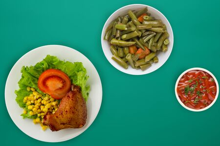 chicken wing with lettuce, corn and tomatoes on a white plate. chicken wing with vegetable salad and sauce on a green background top view