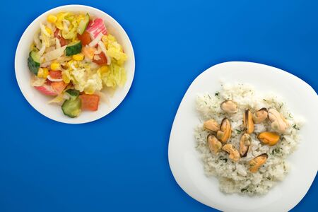 white rice with dill and mussels on a white plate. rice in vegetable salad on a blue background top view. Asian cuisine.flat lay