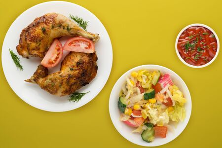 grilled chicken thigh with vegetables on a white  plate  with vegetable salad  on a yellow  background.fast food top view.junk food.flat ley Banco de Imagens