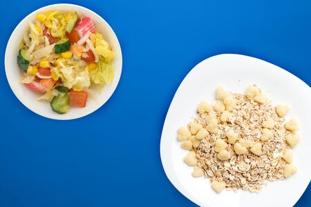 Healthy breakfast on a white plate on a blue background. Muesli with vegetable salad top view