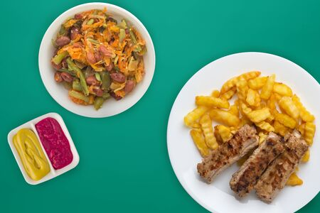 pork ribs and potatoes on a white plate with salad and sauce on a green background. Top view of fast food. unhealthy food.flat lay