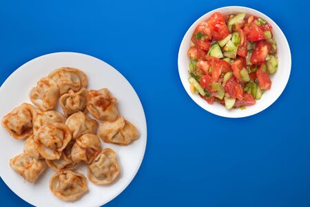 dumplings on a white plate against a blue background. Dumplings meat in tomato sauce with vegetable salad top view. Asian cuisine