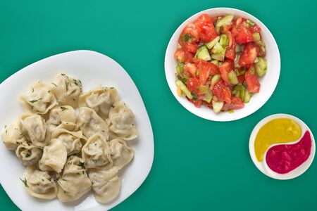 dumplings on a white plate on a green background. Top view of dumplings with vegetable salad. Asian cuisine flat lay Stock Photo - 136988538