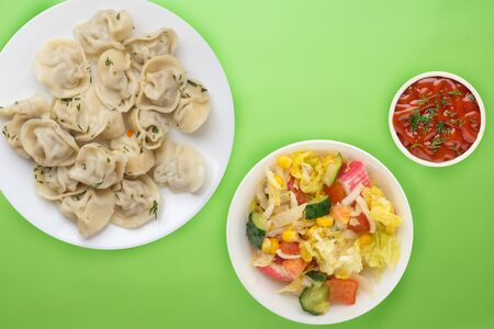 dumplings on a white plate on a lme background. Top view of dumplings with vegetable salad. Asian cuisine flat lay Stock Photo - 137393674