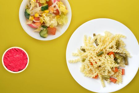 pasta on a white  plate with vegetables on a yellow background. Mediterranean food on with vegetable salad and sauce. healthy food top view. flat lay