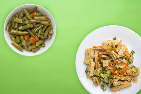 salad with soy asparagus and carrots, cucumbers and dumplings on a white plate. vegetarian soy salad on a plate on a lime background. healthy eating top view.flat lay