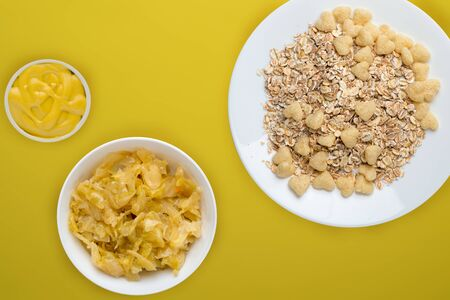 Healthy breakfast on a white plate on a yellow background. Muesli with vegetable salad top view