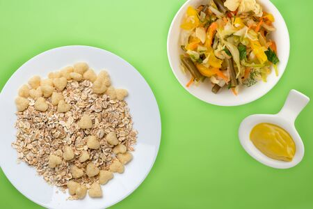 Healthy breakfast on a white plate on a lime background. Muesli with vegetable salad top view Banco de Imagens