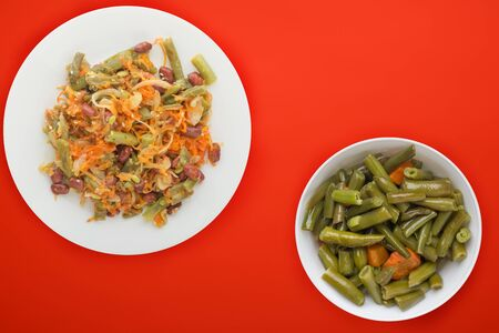 Vegetarian salad. Healthy food. Salad of beans, asparagus, onion, carrot and sesame on a white  plate on a red background. Banque d'images