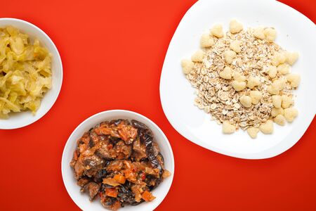 Healthy breakfast on a white plate on a red background. Muesli with vegetable salad top view