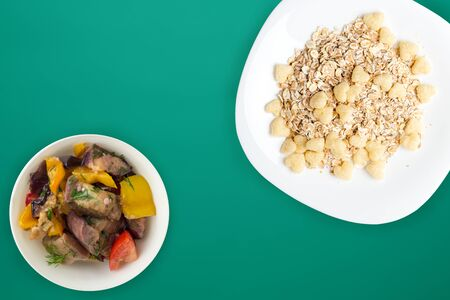 Healthy breakfast on a white plate on a green background. Muesli with vegetable salad top view
