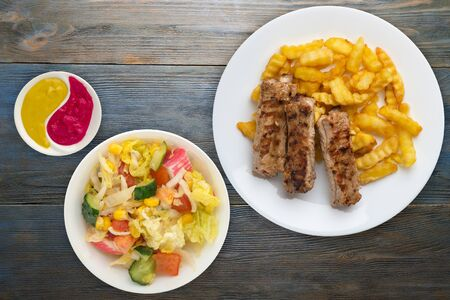 pork ribs and potatoes on a white plate with vegetable salad and sauce on a  gray blue wooden background. Top view of fast food. unhealthy food.flat lay