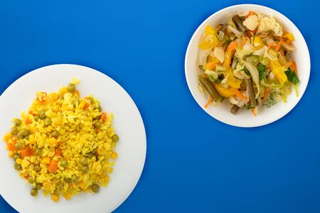 Asian healthy food. yellow rice on a white plate with vegetables. healthy food on a blue background top view.flat lay