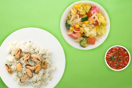 white rice with dill and mussels on a white plate. rice in vegetable salad on a lime background top view. Asian cuisine.flat lay