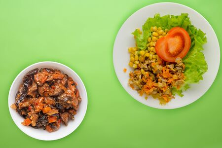 salad with chicken stomachs with carrots and corn and salad on a white plate. chicken salad with vegetables on a lime background Stok Fotoğraf