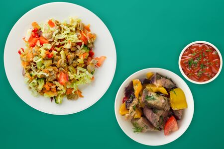 salad with chicken stomachs with vegetables carrots, onions, peppers, cabbage, tomato, broccoli. salad with chicken on a white plate on a green background Stok Fotoğraf