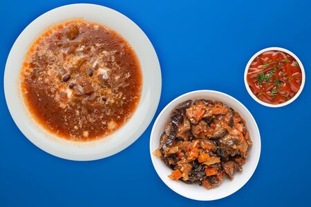 Borscht soup on a blue background. Borscht soup with sour cream and with vegetable salad. healthy lunch top view