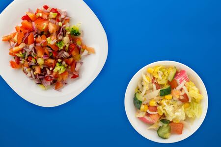 vegan food. salad from vegetables pepper, tomato, onions, broccoli on a white plate. vegan salad on a blue background 스톡 콘텐츠 - 139726468