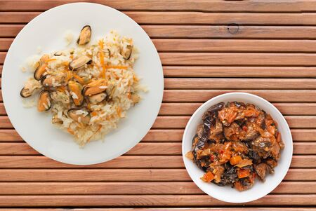 rice with mussels and carrots on a white plate. rice with mussels and carrots on a orange wooden background. rice with vegetable salad and sauce top view.asian food flat lay 스톡 콘텐츠