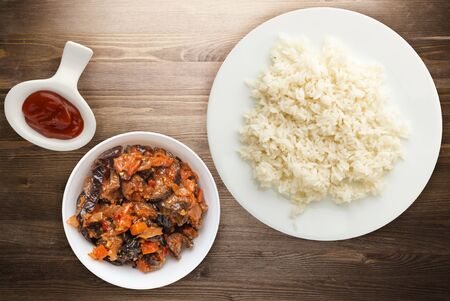 white rice on a white plate. rice with vegetable salad on a brown wooden background top view .asian food
