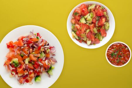 vegan food. salad from vegetables pepper, tomato, onions, broccoli on a white plate. vegan salad on a yellow background 스톡 콘텐츠 - 139726483