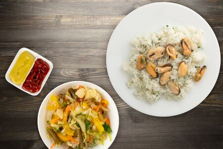 white rice with dill and mussels on a white plate. rice in vegetable salad on a black wooden background top view. Asian cuisine.flat lay