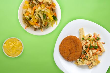fishcake with soy asparagus and carrots, cucumbers and dill. fish cakes on a white plate on a lime background.fish cutlet with vegetables top view 스톡 콘텐츠 - 139726614
