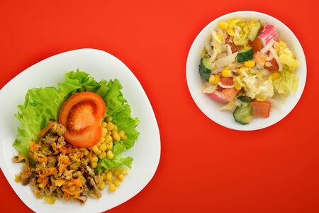 salad with chicken stomachs with carrots and corn and salad on a white plate. chicken salad with vegetables on a red background