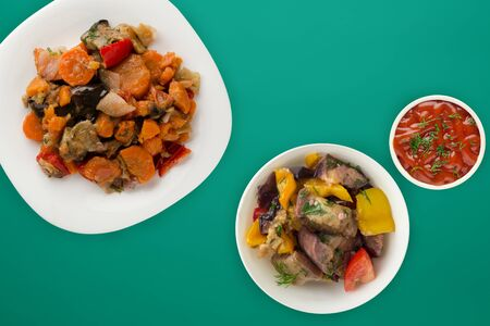 vegetable stew on a white plate. stewed vegetables on a green background. vegetarian food.flat lay