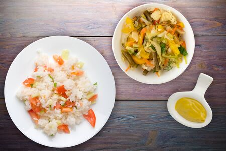 white rice on a white plate. rice with vegetable salad on a purple wooden background top view .asian food