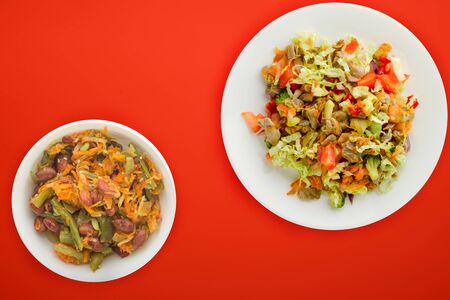 salad with chicken stomachs with vegetables carrots, onions, peppers, cabbage, tomato, broccoli. salad with chicken on a white plate on a red background 스톡 콘텐츠