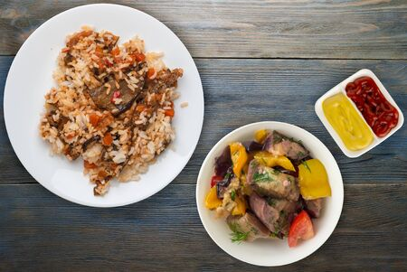 rice with braised zucchini with tomatoes and peppers on a white plate. rice with vegetables on blue wooden background. healthy vegetarian food. Asian cuisine top view