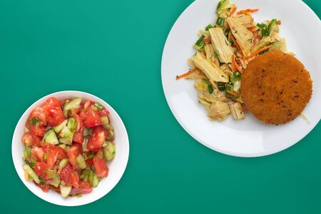fishcake with soy asparagus and carrots, cucumbers and dill. fish cakes on a white plate on a green background.fish cutlet with vegetables top view