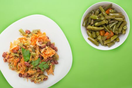 Vegetarian salad. Healthy food. Salad of beans, asparagus, onion, carrot and sesame on a white plate on a lime background.
