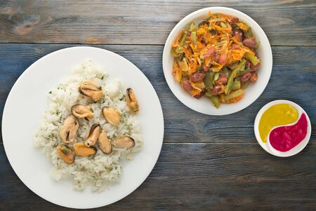 arroz blanco con eneldo y mejillones en un plato blanco. arroz en ensalada de verduras en una vista superior de fondo de madera azul. Cocina asiática endecha plana.