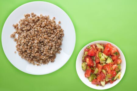 buckwheat in a white plate on a lime background with vegetable salad. buckwheat top view. Healthy food. vegetarian food