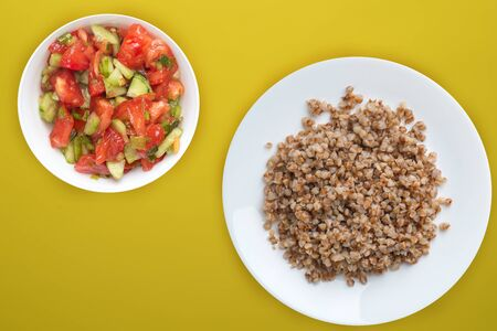 buckwheat in a white plate on a yellow background with vegetable salad. buckwheat top view. Healthy food. vegetarian food