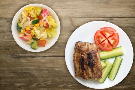 grilled pork ribs with sliced cucumbers and tomatoes on a white plate. pork ribs on wooden background. ribs grill top side view