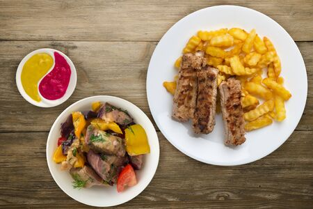 pork ribs and potatoes on a white plate with vegetable salad and sauce on a wooden background. Top view of fast food. unhealthy food.flat lay