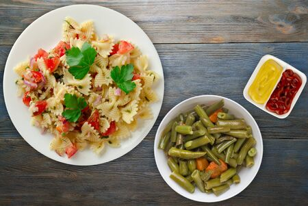 pasta on a white plate. pasta tomatoes, onions, cabbage on a blue wooden background. pasta with vegetarion salad top view