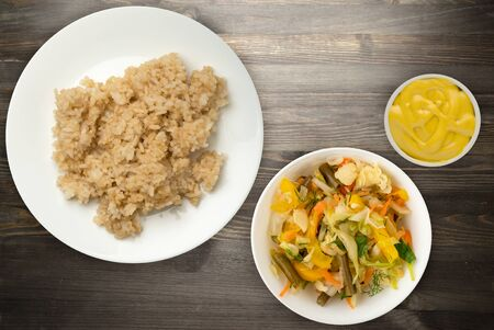 white rice in soy sauce on a white plate. rice with vegetable salad on a black wooden background top view. asian food 스톡 콘텐츠