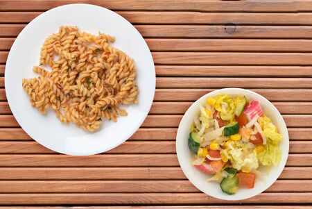 pasta on a white plate isolated on orange wooden background. pasta in tomato sauce with dill. pasta with salad top side view 스톡 콘텐츠