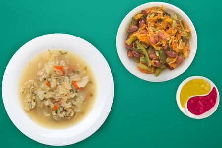 Cabbage soup on a white plate on a green background. soup with vegetable salad. Vegetarian soup. healthy food top view