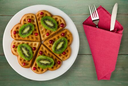 wafers with kiwi and cranberries on a green wooden background. waffles on a white plate with fork and knife top view 스톡 콘텐츠