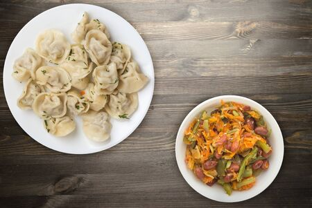 dumplings on a white plate on black wooden background .boiled dumplings with salad.meat dumplings top view .pelmeni with dill 스톡 콘텐츠